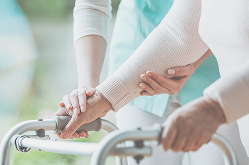 Close of up elderly woman's hand on a walker being assisted by nurses hands